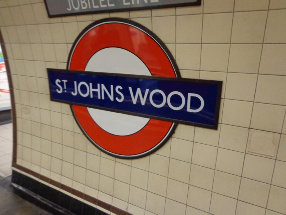A red circle and blue bar reading St Johns Wood at the tube stop of the same name in London
