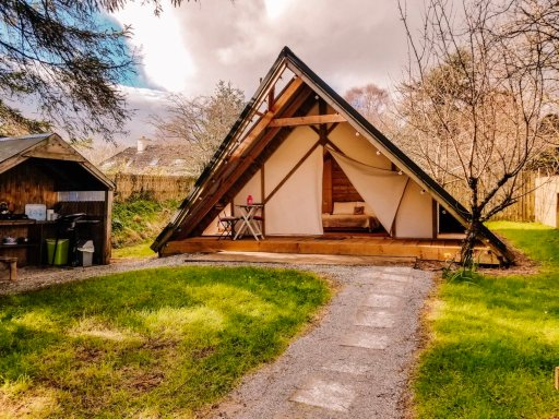 Wooden A-frame glamping tent with a gravel foot path in front of it at Killarney Glamping