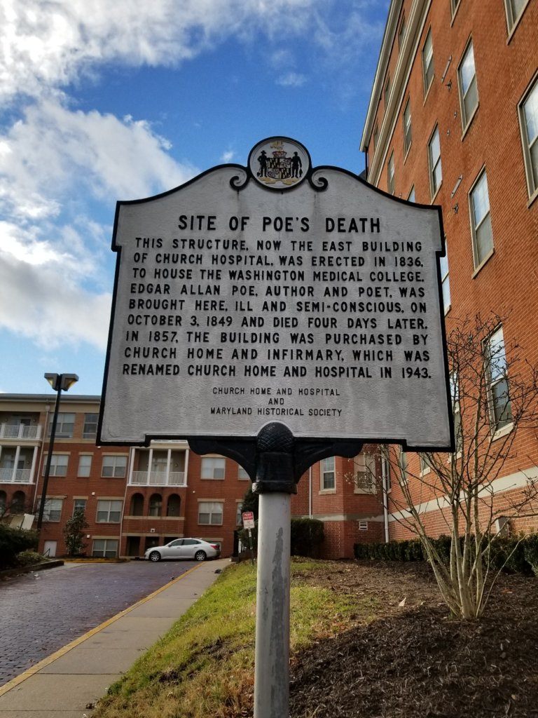 White historical sign that says Site of Poe's Death