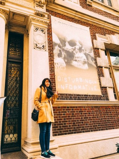 Young woman standing outside a building with a picture of a skull that says 'disturbingly informative - Philadelphia things to do