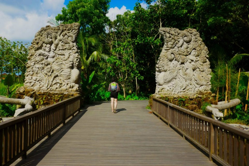 A girl with a backpack walking through the gates of the monkey forest
