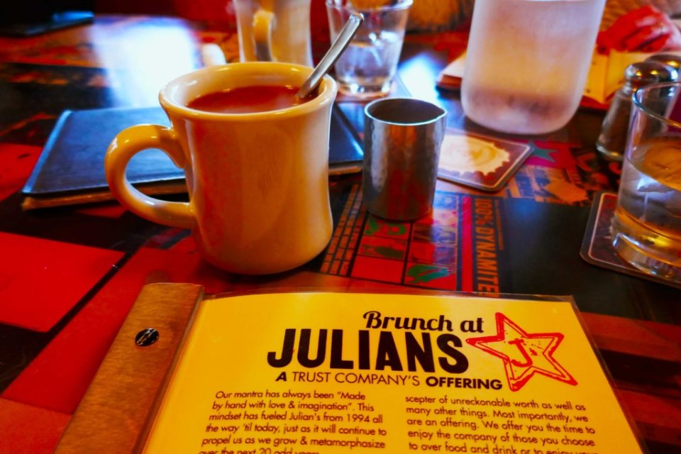 White mug on a checkered table next to a menu that says Julians