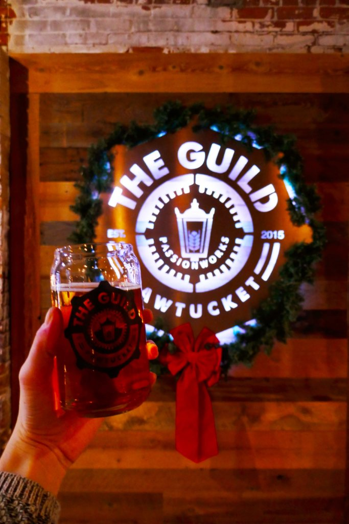 Hand holding up a glass of beer in front of  a metal sign that says The Guild Pawtucket