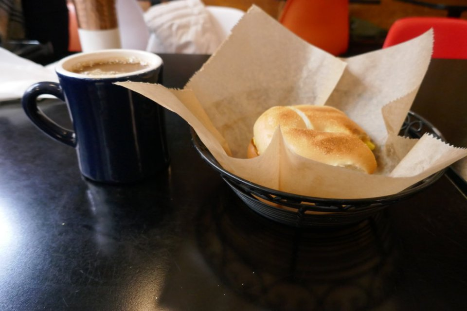 A blue mug of coffee and a basket with a bagel in it