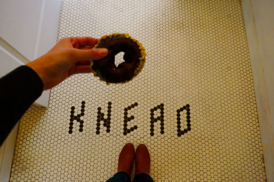 Hand holding a chocolate doughnut above a tile sign that says Knead