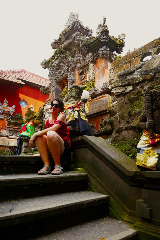 Young woman in a red shirt sitting on the steps of a Balinese temple