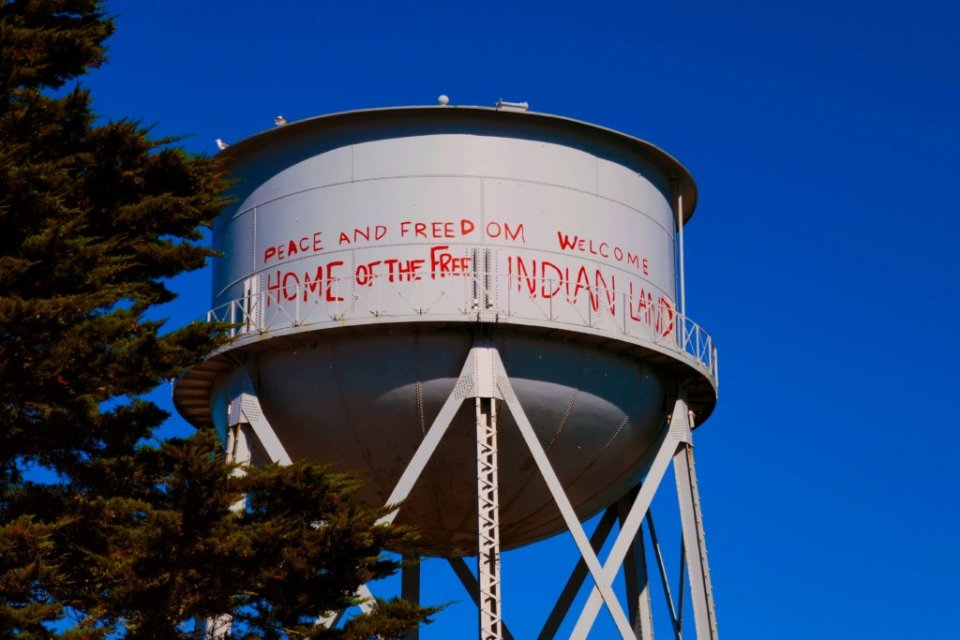 """Water tower that says """"Welcome to Indian Land"""" in red spray paint"""