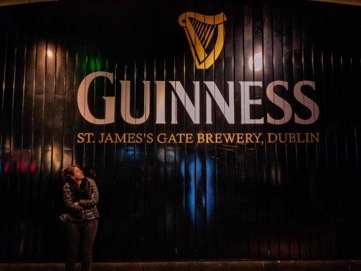 Young woman in front of black Guinnnes door in Dublin Ireland