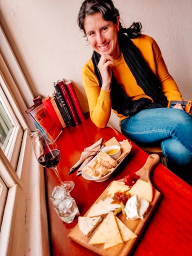 Me sitting in front of a cheeseboard and glass of wine at Sheridans Cheesemongers in Galway Ireland during our self drive tour of Ireland