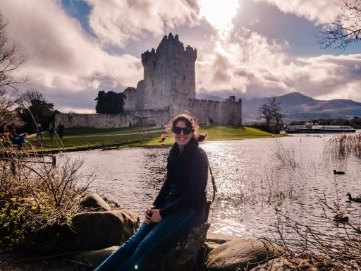 Young woman in a black coat sitting across the water from Ross' Castle in Killarney Ireland