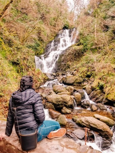 Young woman in a black coat sitting looking at Torc Waterfall in Killarney Ireland