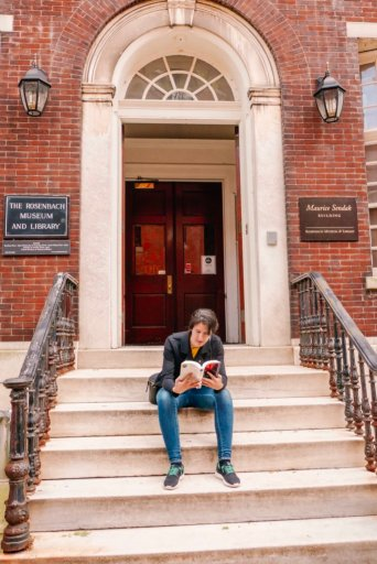 A young woman sitting, reading a book on the steps of the Rosenbach museum in Philadelphia