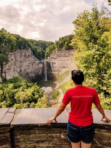 Back of a woman standing facing Taughannock Falls - one thing to do in Watkins Glen