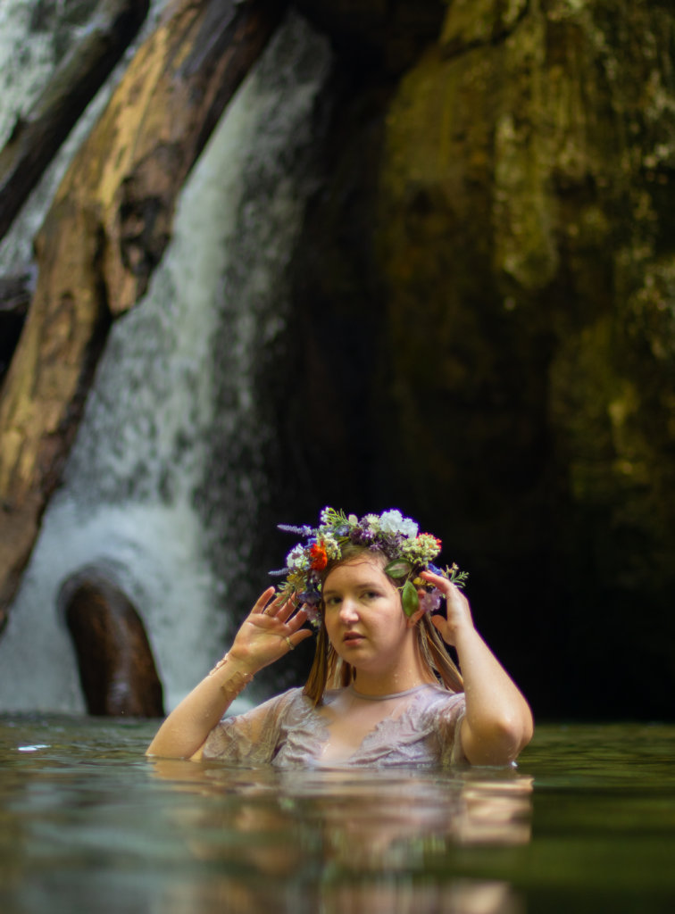 Girl in a purple dress in the water with a flower crown at Kilgore Falls photo shoot