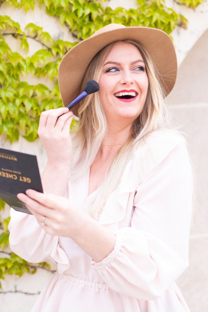 Renee, a white woman with blonde hair, puts on blush with a brush in front of a wall of ivy with a pink ruffled shirt on along with red lipstick and a hat.