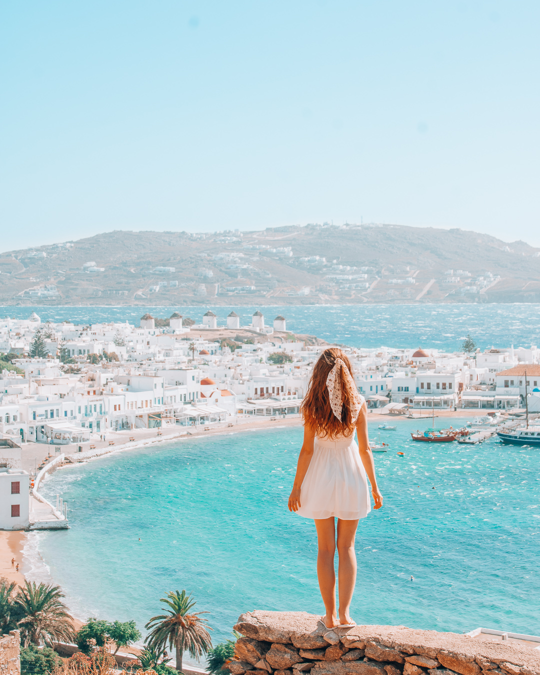 Girl looking at Mykonos Town and the windmills from above