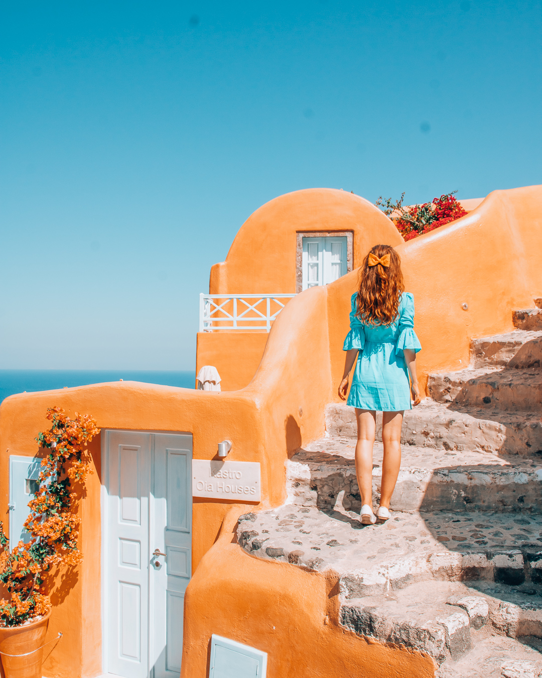Girl with blue dress and orange bow at the stairs of Kastro Oia Houses