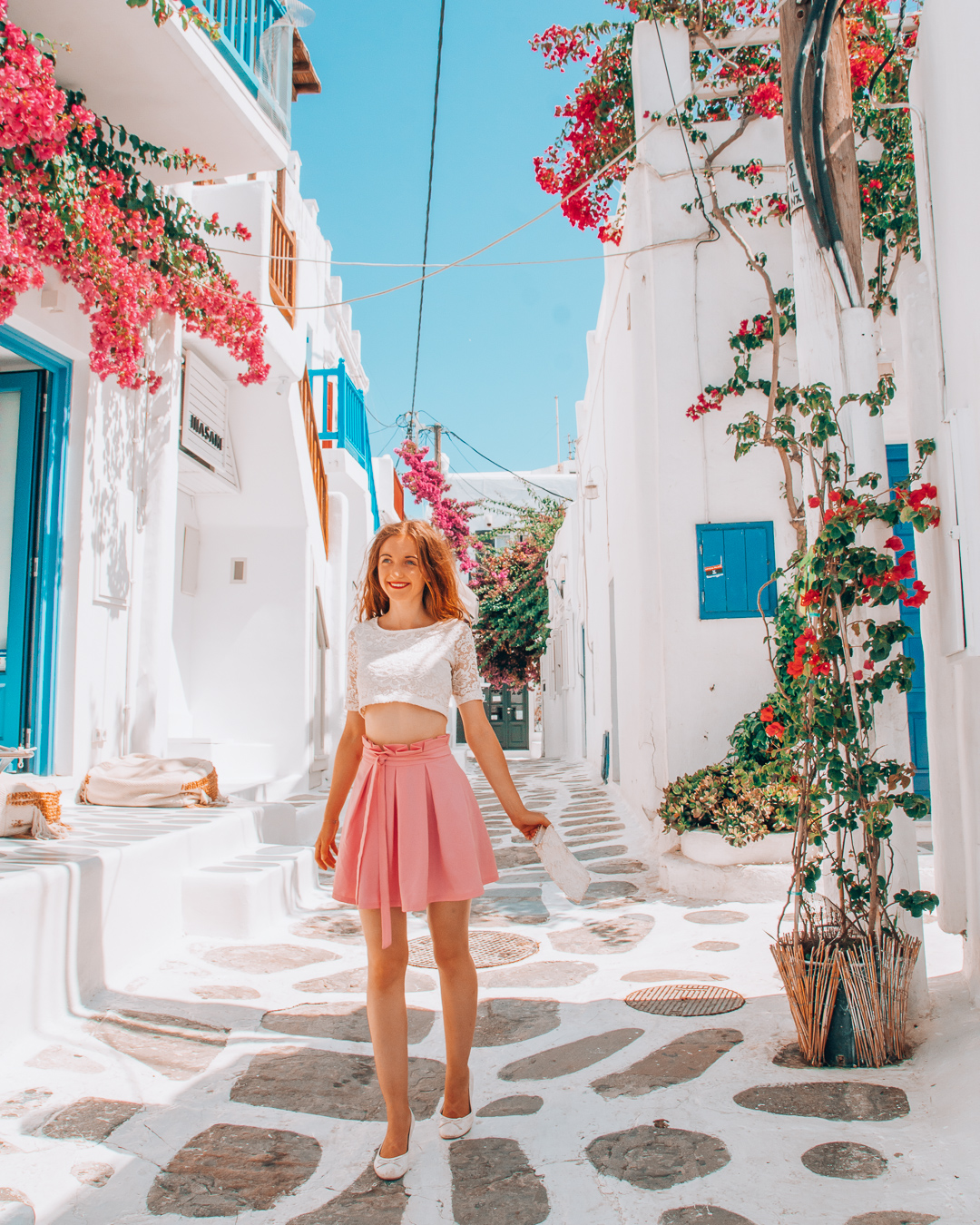 Happy girl in a colourful street with flowers