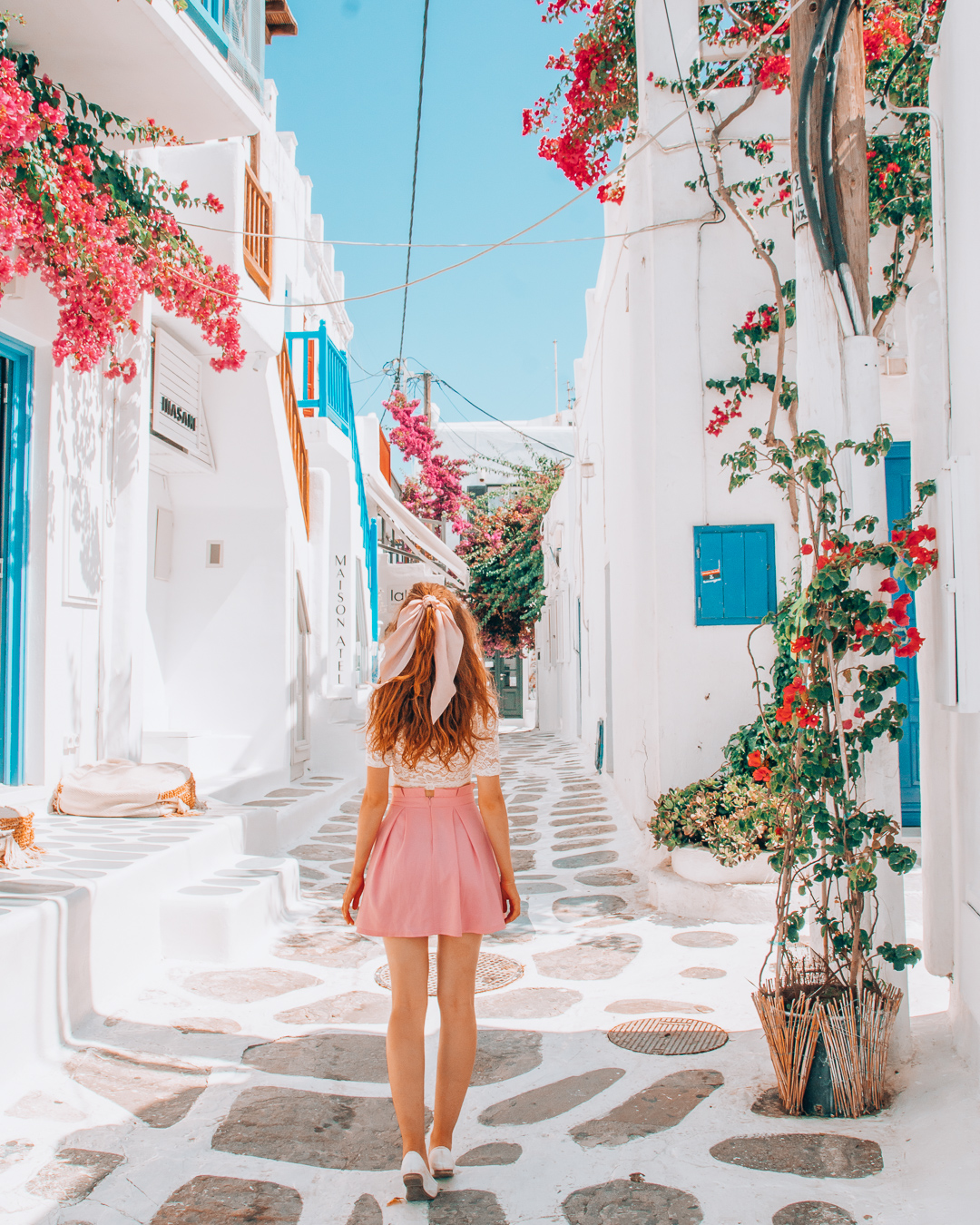 Girl in a colourful street with flowers in Mykonos