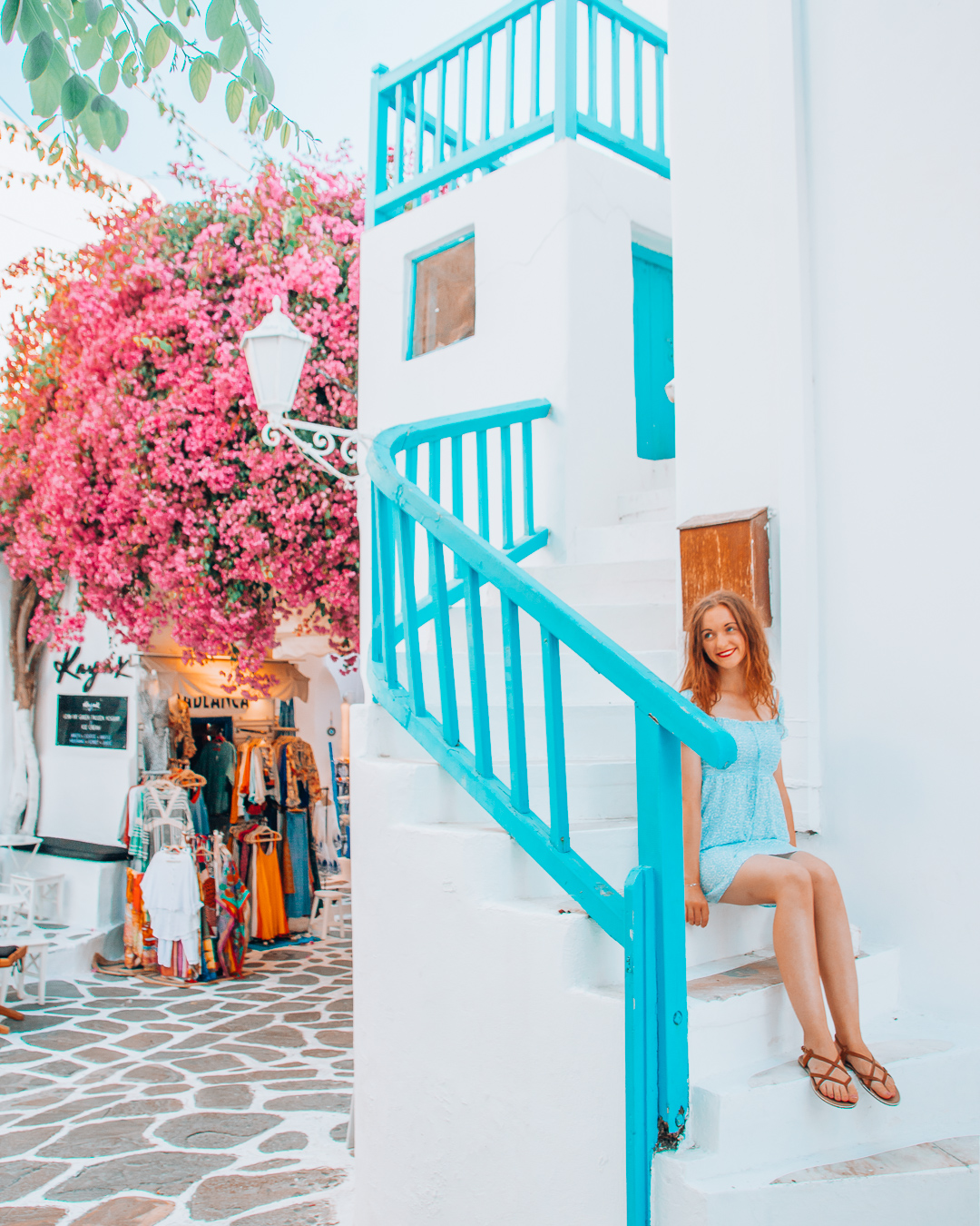 Girl sitting on stairs in Mykonos and a pink tree