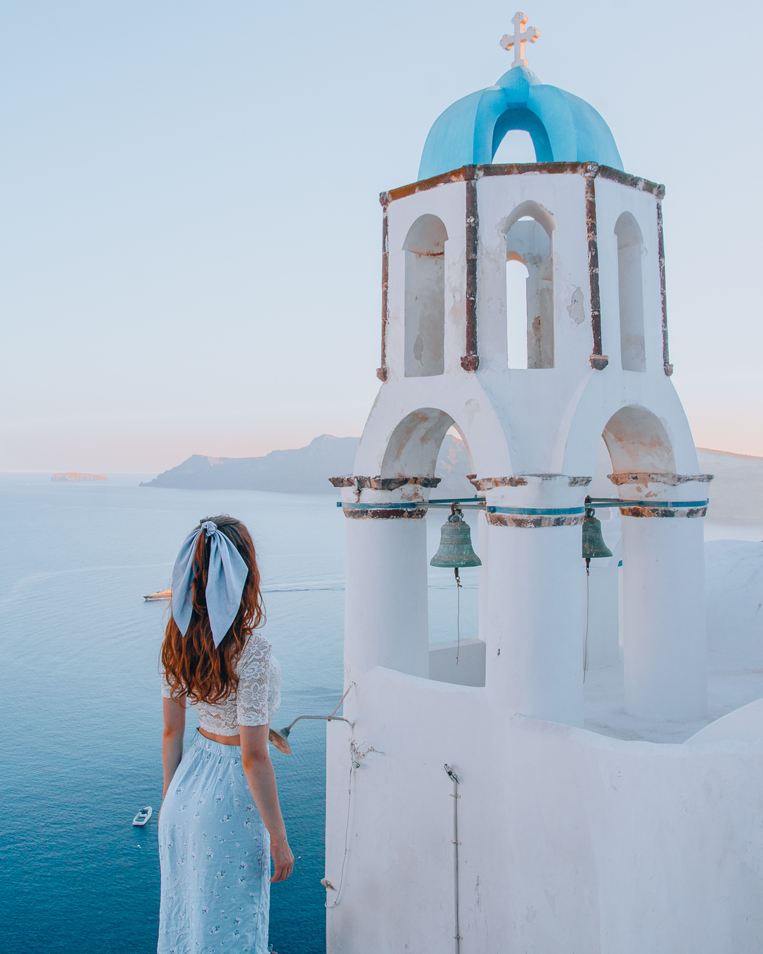 Girl next to a bell tower in Santorini