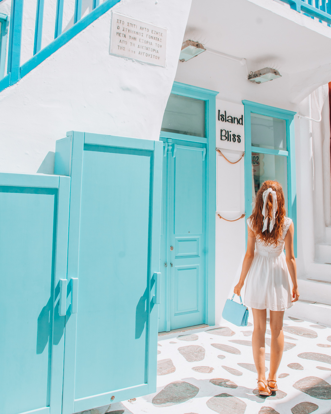Girl with a white dress and a blue bag looking at a blue building in Mykonos