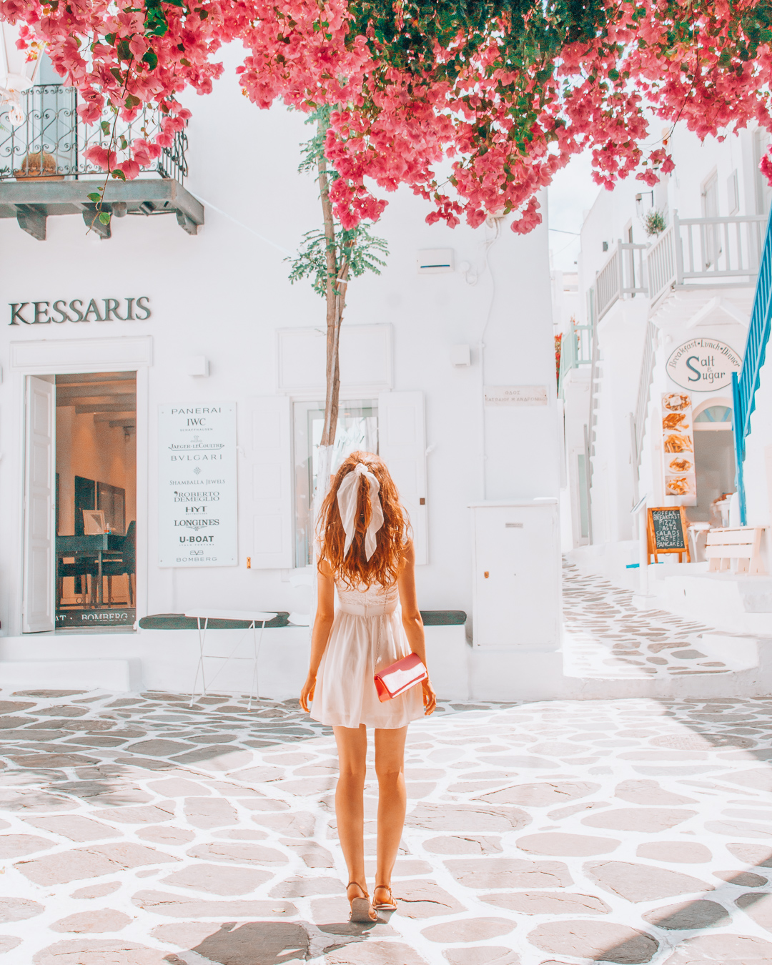 Girl walking in Mykonos, pink flowers, a shop and a restaurant