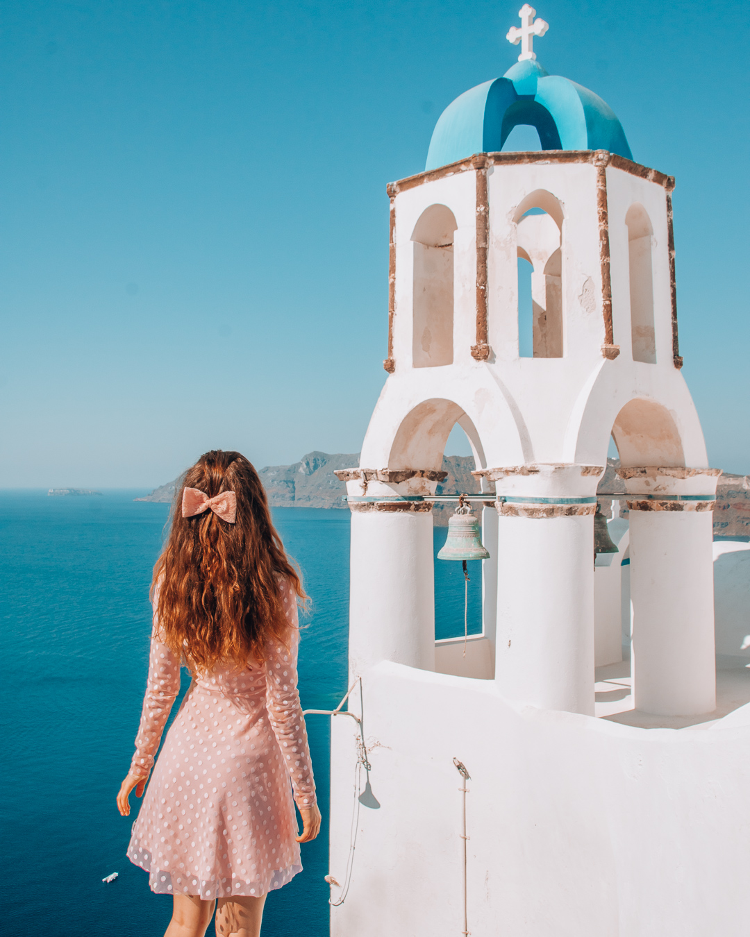 GIRL with a pink dress NEXT TO a BELL TOWER in Santorini