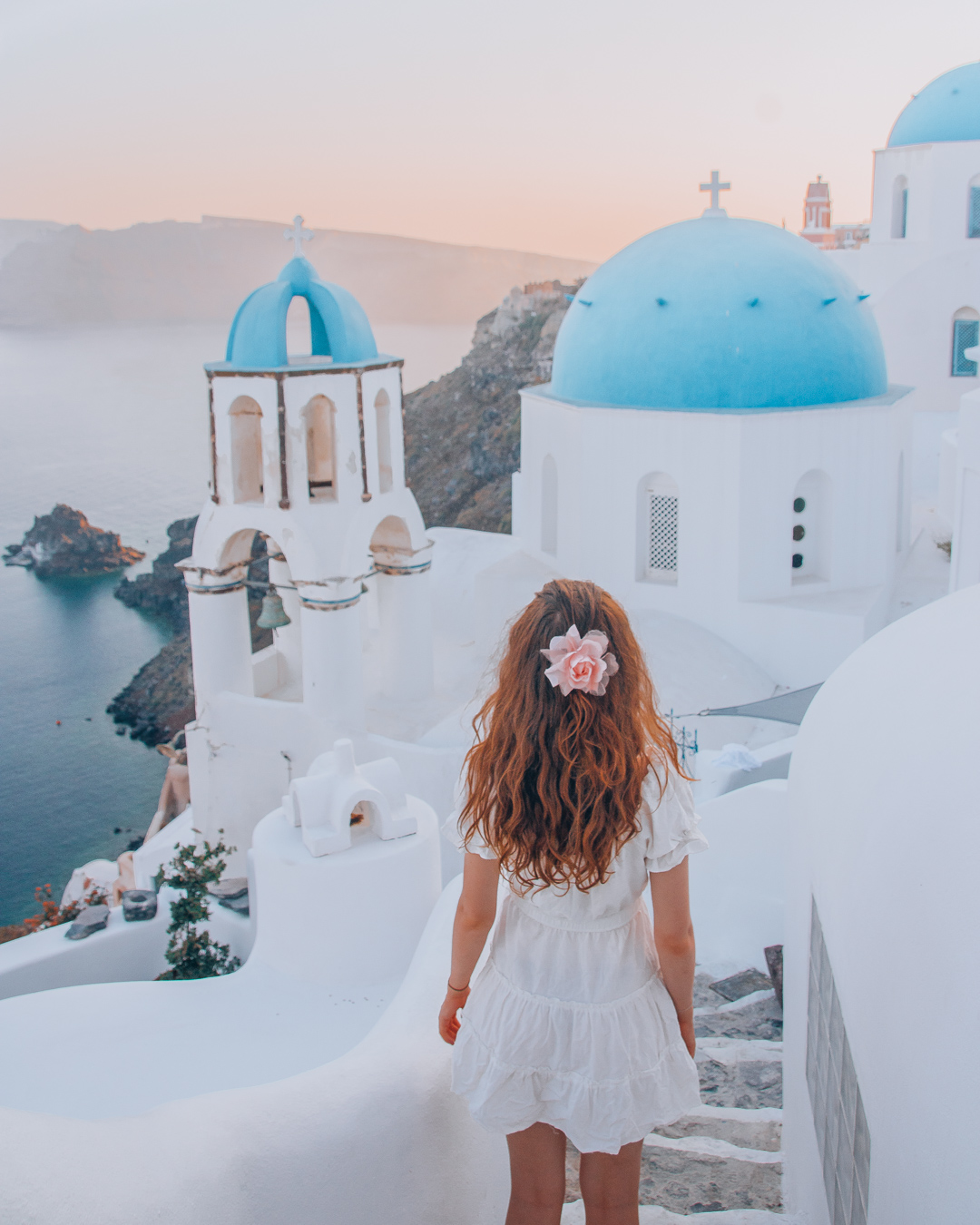 Girl looking at the sunset in front of the blue domes in Santorini