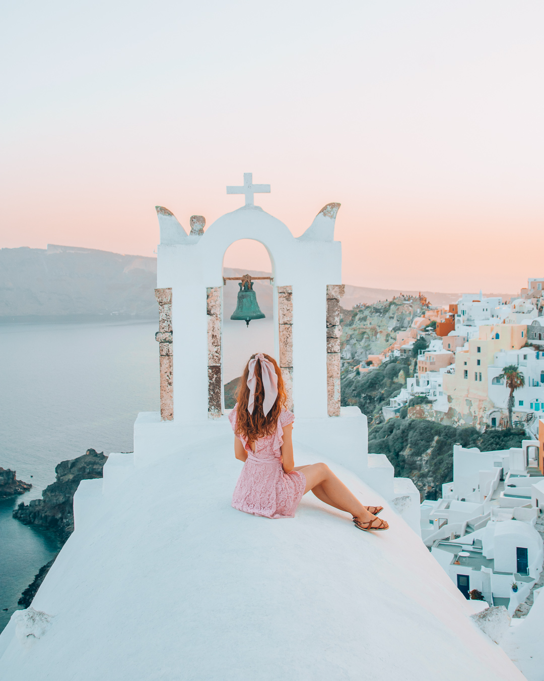 GIRL sitting ON TOP OF A CHURCH with a view over Oia