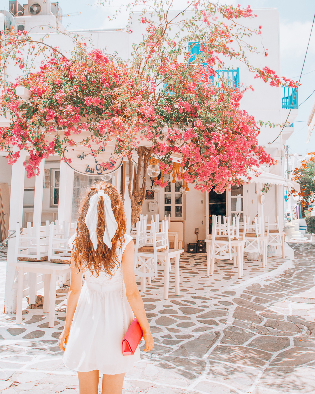 Girl looking at Busulas in mykonos and a pink tree