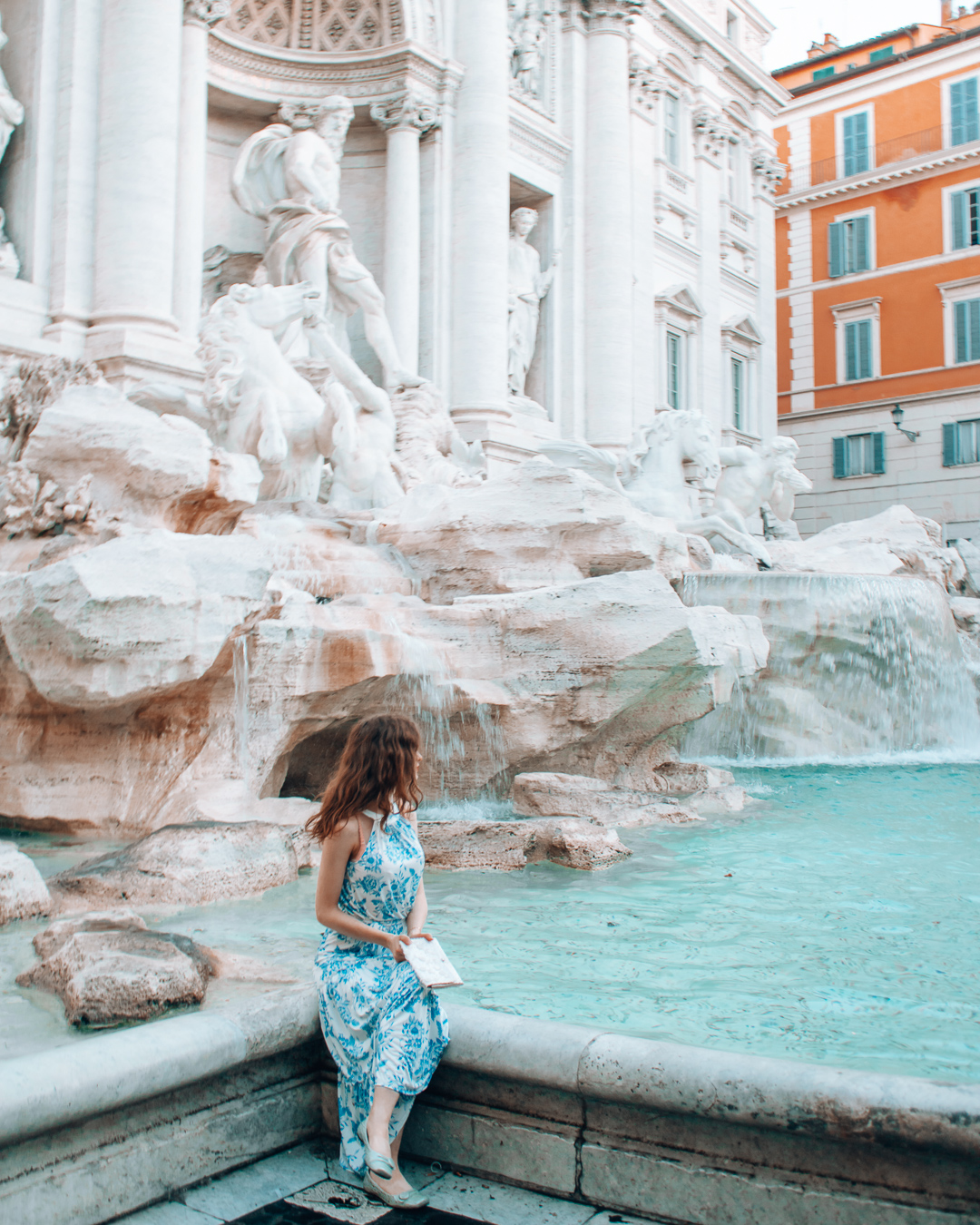 Girl sitting at the Trevi Fountain