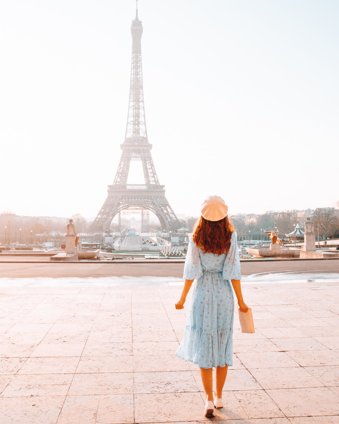 A girl with a blue dress in front of the Eiffel Tower in Paris