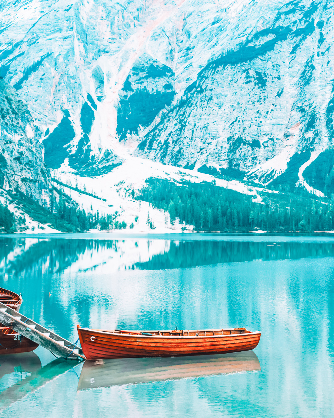 Blue water and a boat at a lake in the  Dolomites