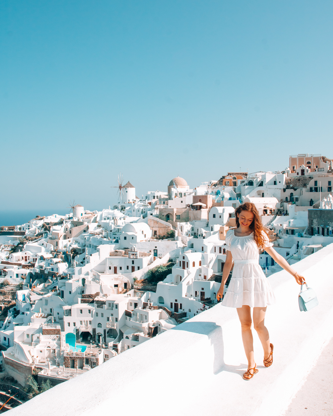 Happy girl at Oia Castle and view of white houses in Santorini
