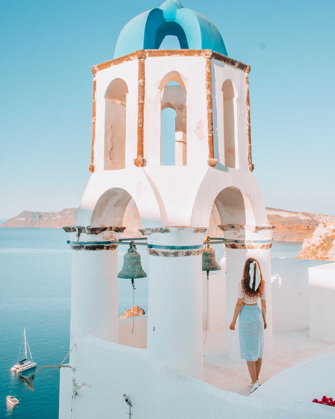 Girl looking at a bell tower in Santorini