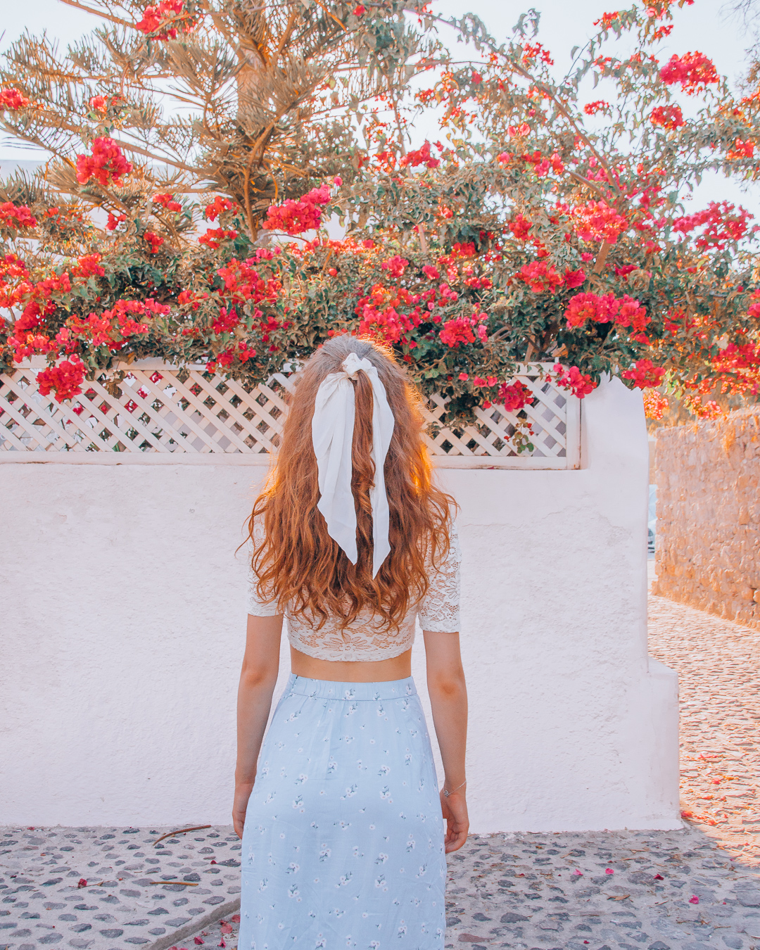 Girl and wall with red flowers in Santorini