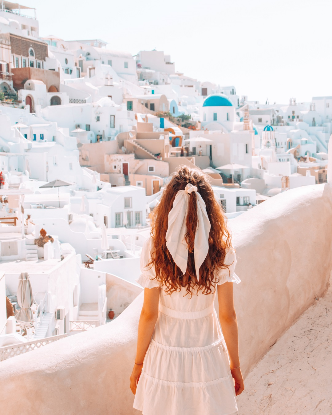 Girl solo in Santorini looking at white houses
