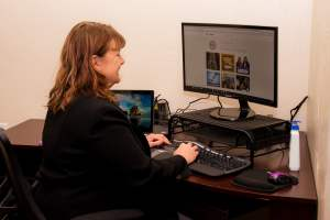 A woman at a desk working on her computer