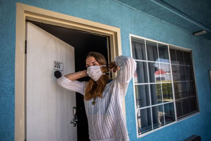 A homeless woman puts her mask on in a motel room provided to the homeless under the