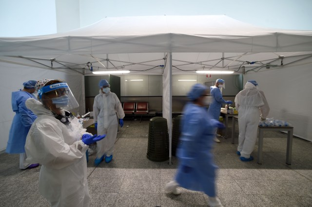 Healthcare professionals work to test travelers for Covid-19 at Malpensa Airport in Somma Lombardo, Italy, on August 20.