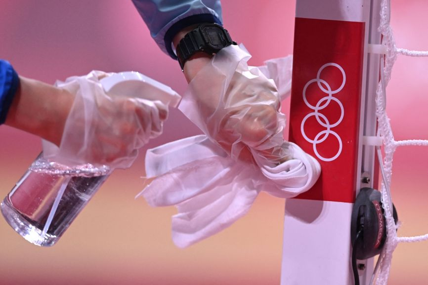 An employee disinfects a handball goal post on July 24.