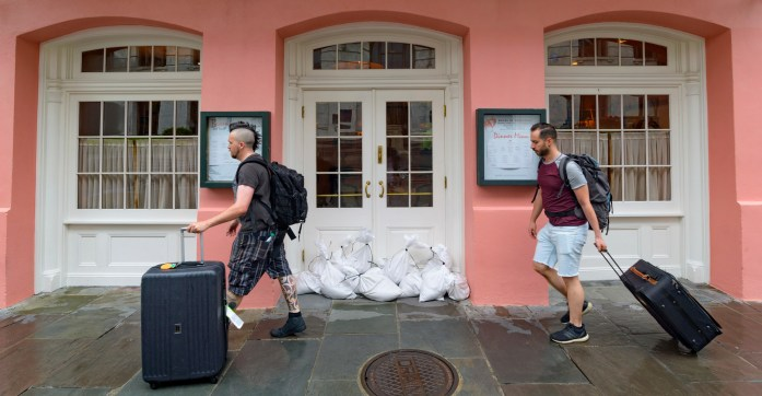 People walk past Brennan's restaurant in the French Quarter with sandbags on the front door as bands of rain from Tropical Storm Barry from the Gulf of Mexico move into New Orleans on July 12, 2019.