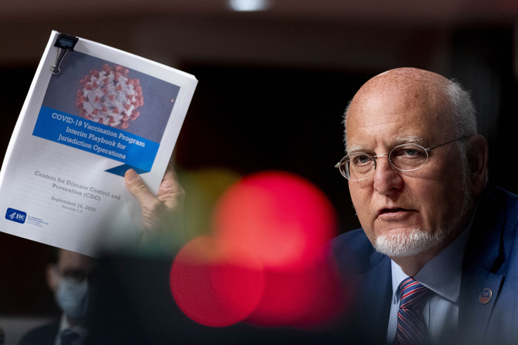 Dr. Robert Redfield holds up a CDC document while he speaks at a hearing of the Senate Appropriations subcommittee reviewing coronavirus response efforts on September 16 in Washington.