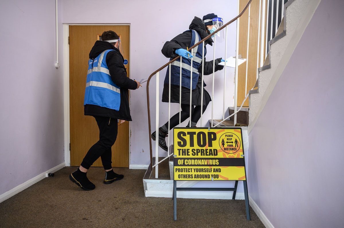 Volunteers deliver Covid-19 test kits to the doors of residents near Muswell Hill on March 22 in London, England.