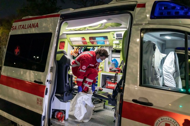 Marco Vangelista, a member of the Italian Red Cross ambulance team, puts on protective equipment while responding to the emergency of a coronavirus patient April 8 in Bergamo, Italy.
