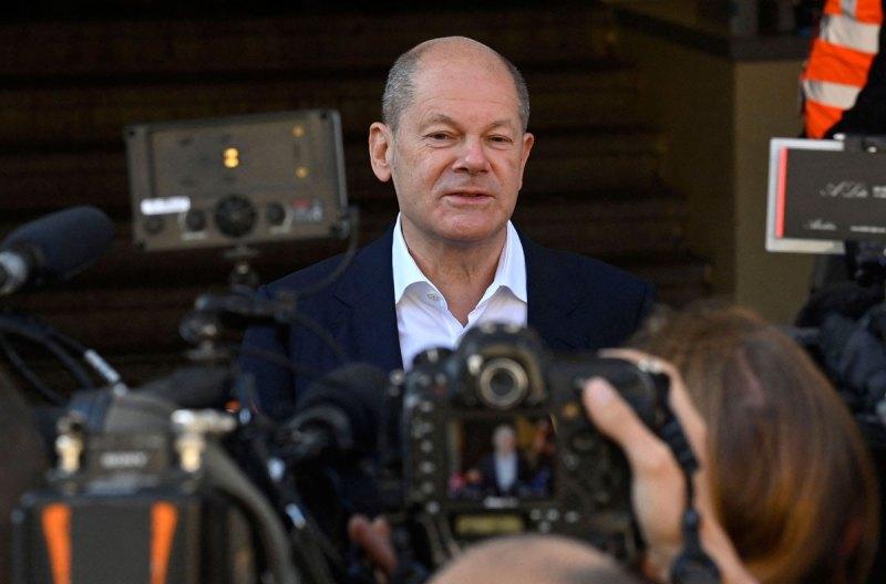 Olaf Scholz parla ai giornalisti dopo aver votato in un seggio elettorale a Potsdam, in Germania.