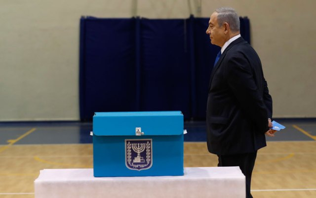 Israeli Prime Minister Benjamin Netanyahu prepares to cast his ballot during the Israeli legislative elections at a polling station in Jerusalem.
