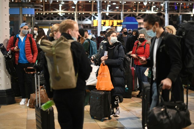 People wait on the concourse at Paddington Station in London on December 19 ahead of the introduction of tougher new restrictions.