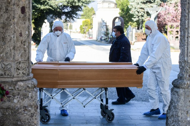 Undertakers wearing faces mask and overalls unload a coffin out of a hearse on March 16, at the Monumental cemetery of Bergamo, Lombardy, Italy.